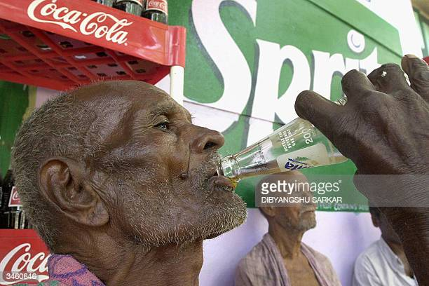 An Indian villager drinks bottle of Coca Cola owned soft drink Fanta during a visit by Coca Cola company Vice President for India Sunil Gupta in...