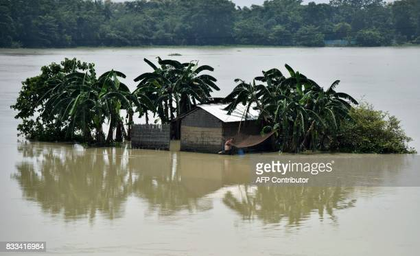 TOPSHOT An Indian villager fishes as floodwaters surround a structure in Morigoan district in Indias northeastern state of Assam on August 17 2017 At...