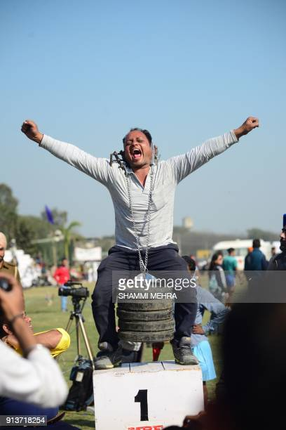 aN Indian villager lifts 60kg weight with his ears during the second day of the Kila Raipur Games popularly known as the rural Olympics at Kila...