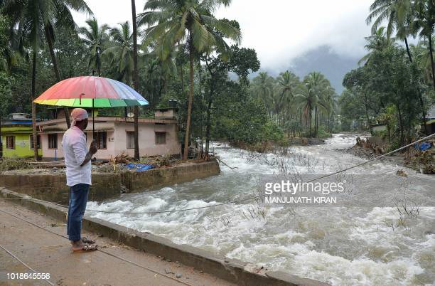 An Indian villager looks at the overflowing Kannappanakundu river in Kozhikode district about 422 km north of Trivandrum in the south Indian state of...