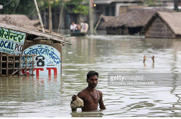 An Indian villager makes his way through the flooded village of Muzaffarpur some 100 kms north of Patna 06 August 2007 Among the millions of people...