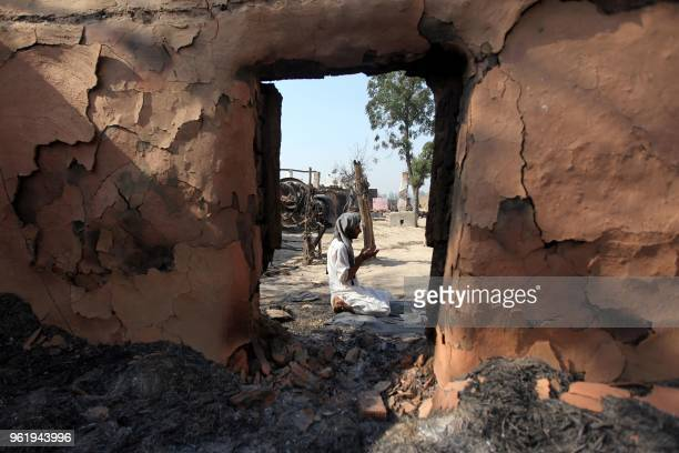 TOPSHOT An Indian villager performs prayers outside his house which was gutted following firing from the Pakistan border at Jora farm village in...