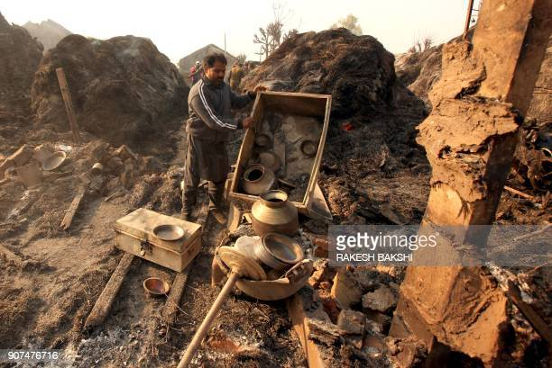 An Indian villager sorts through belongings brought from his house that was damaged in shelling across the IndiaPakistan border in Kapoorpur village...