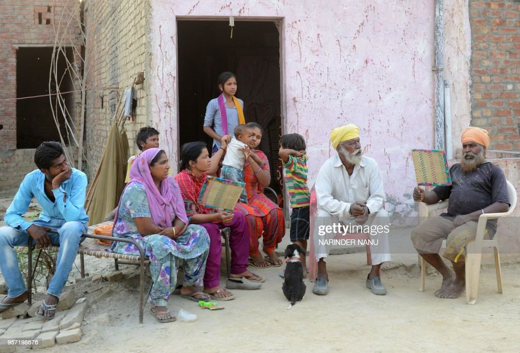 An Indian villager uses a fan as he sits with relatives outside their home in Indra Colony near Wadali village on the outskirts of Amritsar on May 10.