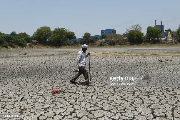 An Indian villager walks on the dried bed of a pond at Vinzol village on the outskirts of Ahmedabad on May 3 2019 Gujarat state is experiencing acute...