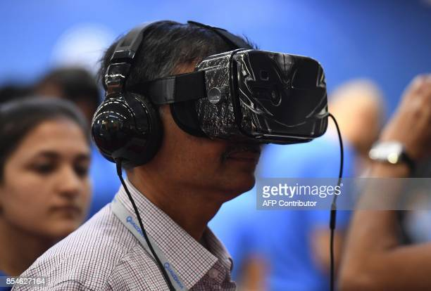 An Indian visitor checks a virtual device at the Qualcomm stall during the India Mobile Congress in New Delhi on September 27 2017 The theme of IMC...