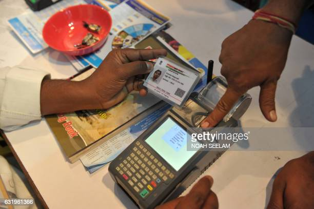 An Indian visitor gives a thumb impression to withdraw money from his bank account with his Aadhaar or Unique Identification card during a Digi Dhan...