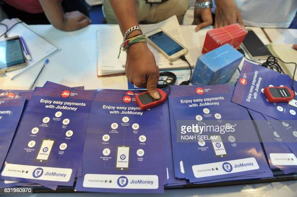An Indian visitor gives a thumb impression to withdraw money from Jio Easy Money outlet with his Aadhaar or Unique Identification card during a Digi...