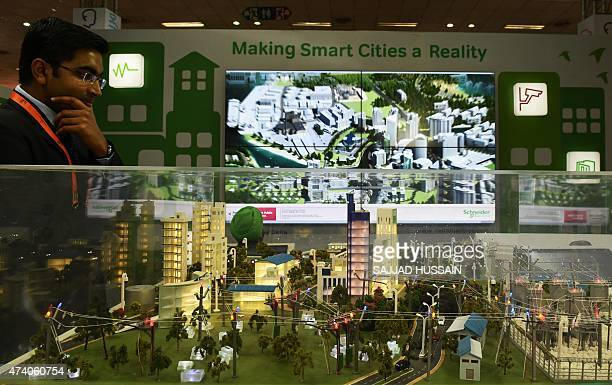 An Indian visitor looks at a model of a 'smart city' at the Smartcity Expo in New Delhi on May 20 2015 The expo is showcasing sustainable living and...