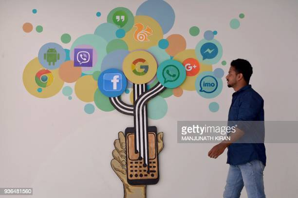 An Indian visitor passes a mural depicting various social medias including Facebook inside a building in Bangalore on March 22 2018 India March 21...
