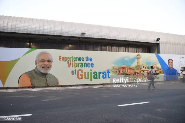 An Indian visitor passes by a hoarding depicting Indian Prime Minister Narendra Modi and Gujarat state Chief Minister Vijaybhai Rupani on the eve of...
