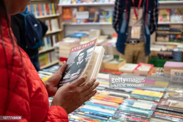 An Indian visitor picks up a copy of Anne Frank 'The diary of a young girl' at the 27th edition New Delhi Book Fair one of Indias longestrunning book...