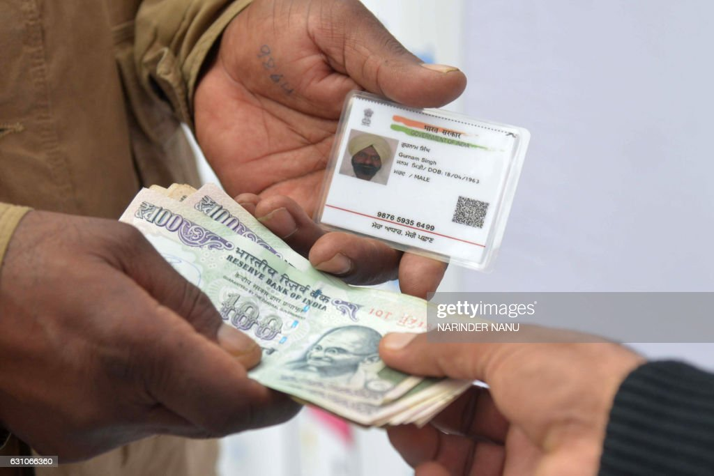 An Indian visitor withdraws money from his bank account with an Aadhaar or Unique Identification card during a Digi Dhan Mela held to promote digital.