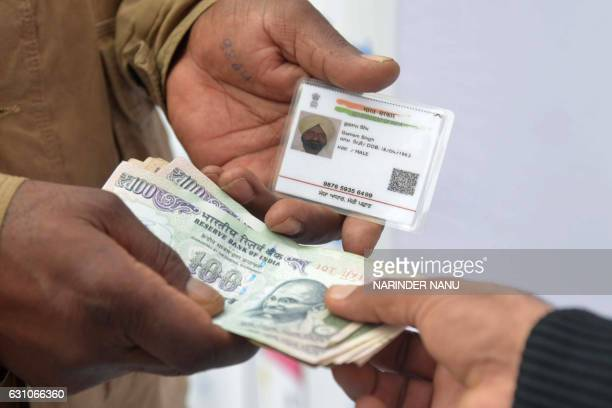 An Indian visitor withdraws money from his bank account with an Aadhaar or Unique Identification card during a Digi Dhan Mela held to promote digital...