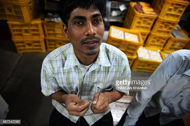 An Indian visuallyimpaired worker threads a needle at a workshop at the Blind School Relief Association in New Delhi on October 15 2014 The...