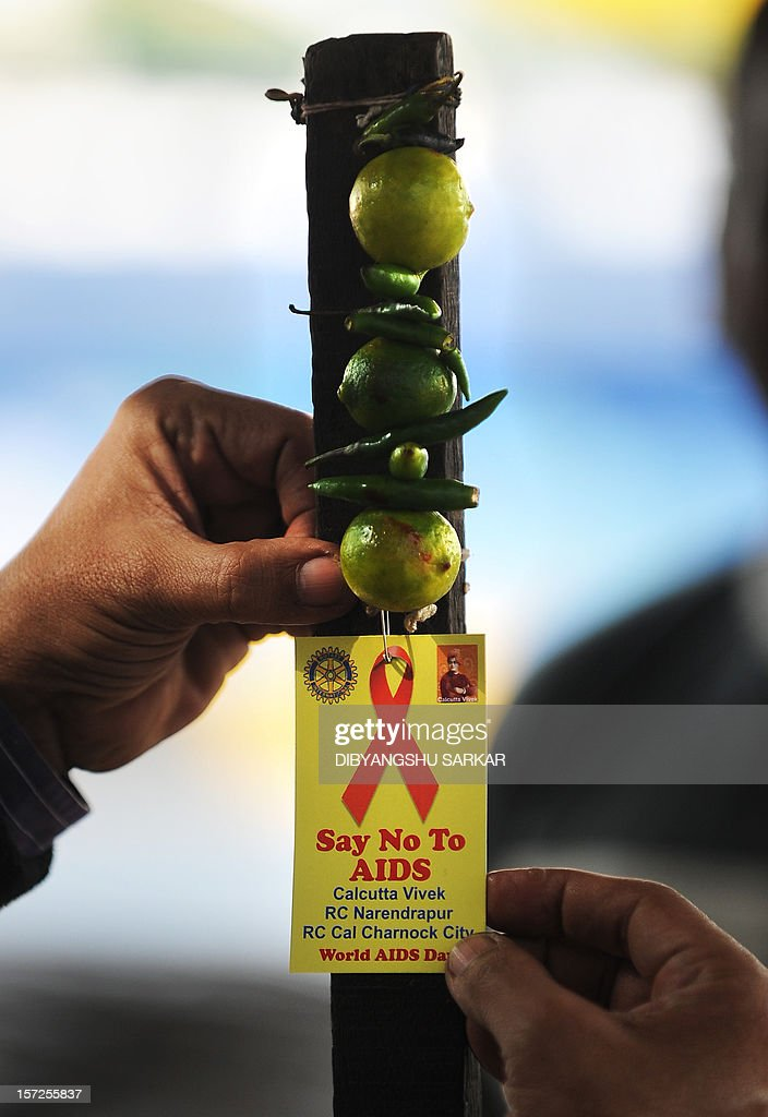 An Indian volunteer adjusts a HIV/AIDS awareness badge on a roadside tea stall during a rally to celebrate World AIDS Day in Kolkata on December 1, 2012. The UNAIDS agency says some 2.5 million Indians are living with HIV, many of them ostracised by their communities. AFP PHOTO/Dibyangshu SARKAR