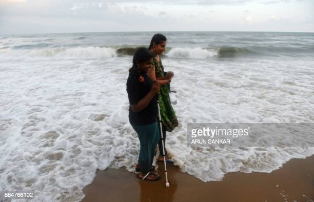 TOPSHOT An Indian volunteer helps a visually impaired girl to take a walk at Elliot's Beach in Chennai on December 3 2017 People with disabilities...