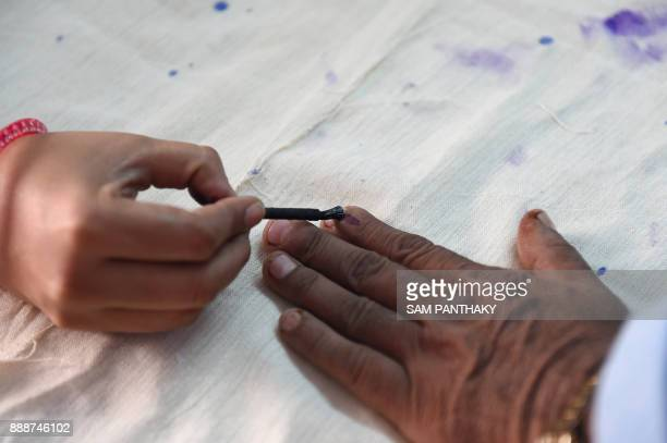 An Indian voter gets his finger inked as he prepares to cast his ballot during the first phase of Vidhan Sabha elections of Gujarat state in Limbdi...