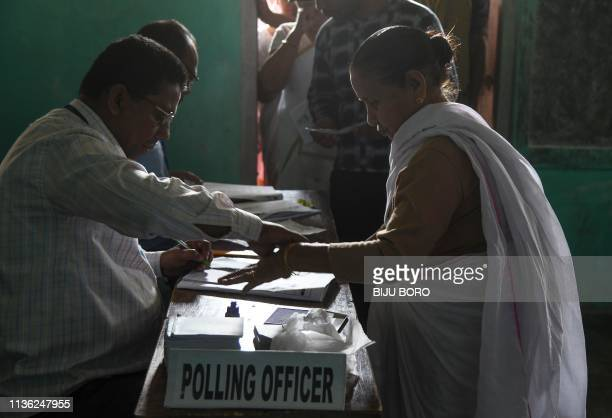 An Indian voter gives her fingerprint as she comes to cast her vote at a polling station during India's general election in Purandudam village some...