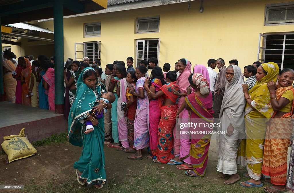 An Indian voter, seen carrying her child, walks past other voters waiting in line outside a polling stating after casting her vote in Dibrugarh on April 7, 2014, during national elections. Indians have begun voting in the world's biggest election which is set to sweep the Hindu nationalist opposition to power at a time of low growth, anger about corruption and warnings about religious unrest. India's 814-million-strong electorate are forecast to inflict a heavy defeat on the ruling Congress party, in power for 10 years and led by India's famous Gandhi dynasty. AFP PHOTO/Dibyangshu SARKAR