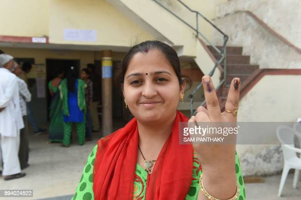 An Indian voter shows both of her inked fingers after voting at a repolling centre at Nava Naroda on the outskirts of Ahmedabad on December 17 2017...