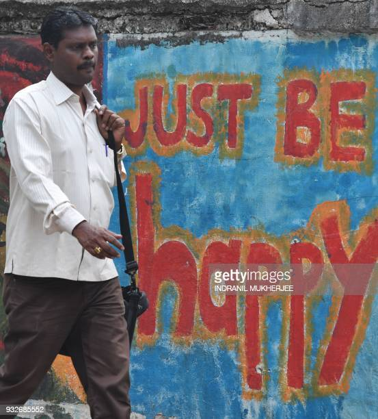An Indian walks past wall graffiti in Mumbai on March 16 2018 The annual World Happiness Report 2018 by United Nations Sustainable Development...