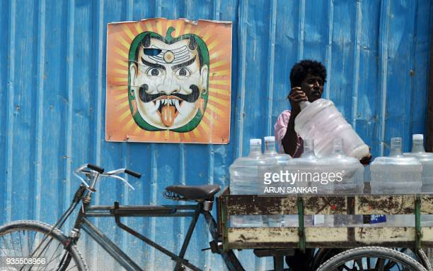 TOPSHOT An Indian water vendor loads his cart with 20 litre water bottles in Chennai on March 21 2018 International World Water Day is marked...