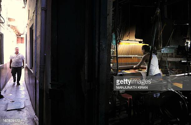 An Indian weaver works on a silk saree using a power loom in a small scale weaving unit in Bangalore on February 28 2013 Indian finance minister P...