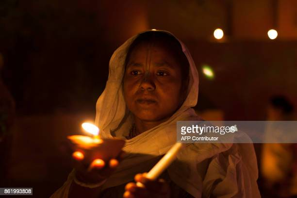 An Indian widow holds an earthen lamp or 'diya' during Diwali celebrations at Gopinath temple in Vrindavan on October 16 2017 Diwali the Festival of...