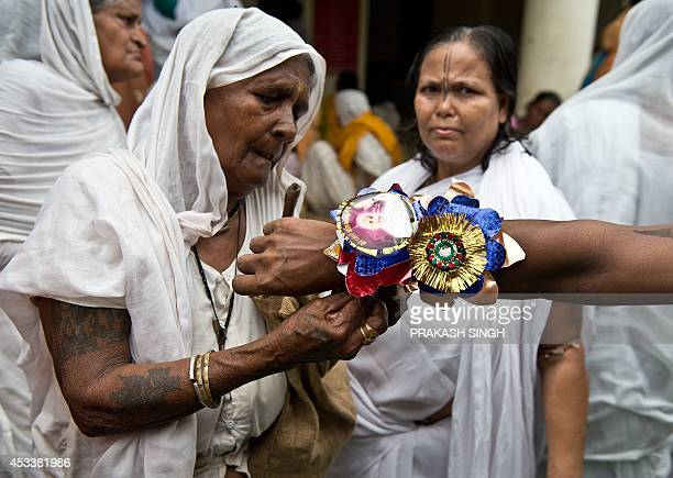 An Indian widow ties a 'rakhi' or sacred threads around the wrist of a holy man during celebrations for the Rakha Bandhan festival at the Meera...