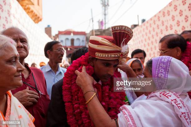 An Indian widow welcomes the groom Rakesh Kumar with garlands at Gopinath temple in the Vrindavan on October 16 2017 India has the greatest number of...