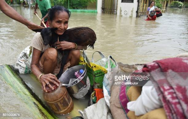 An Indian woamn holds a goat while sitting on a raft at the flood affected Koliabor village some 186km from Guwahati the capital city of Indias...