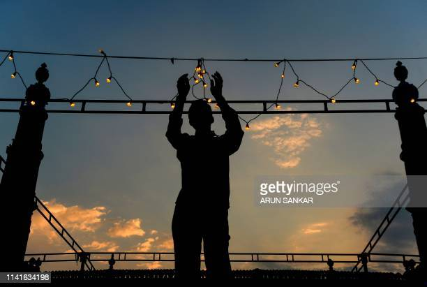 An Indian woker puts on garlands of lights ahead of the start of the holy fasting month of Ramadan at the Wallajah Mosque in Chennai on May 6 2019...