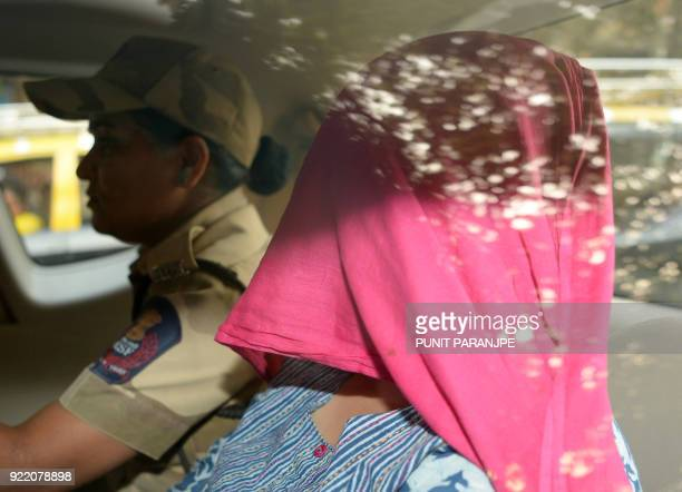 An Indian woman accused in the Punjab National Bank fraud case is escorted after her appearance in the special CBI court in Mumbai on February 21...