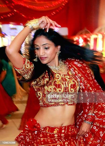 An Indian woman adorning traditional attire performs the Garba dance marking The Navratri Festival at the Gujarati Hindu Sanskruti temple in Durban...