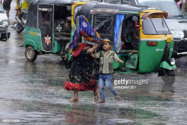 TOPSHOT An Indian woman and child cross a road in heavy rain brought by Cyclone Mora in Agartala the capital of northeastern state of Tripura on May...