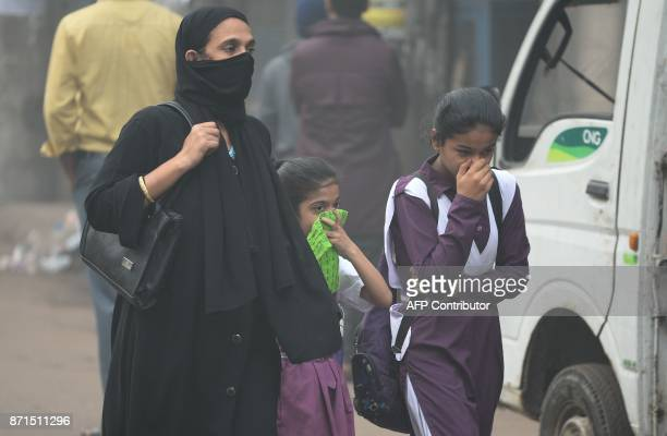 An Indian woman and children walk amid heavy smog in New Delhi on November 8 2017 Delhi shut all primary schools on November 8 as pollution levels...
