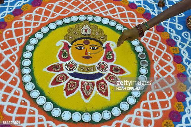 An Indian woman applies colored powder to a 'rangoli' hindu ritual design during a competition in Hyderabad on January 13 on the eve of the...