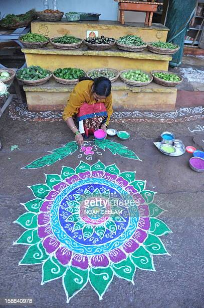 An Indian woman applies coloured powder to her 'rangoli' a Hindu ritual design in front of her house in Hyderabad on January 1 2013 Rangolis are...