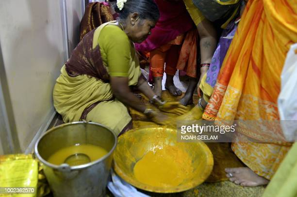 An Indian woman applies turmeric powder to the feet of women devotees before offering prayers to Hindu goddess Mahakali ahead of the Bonalu festival...