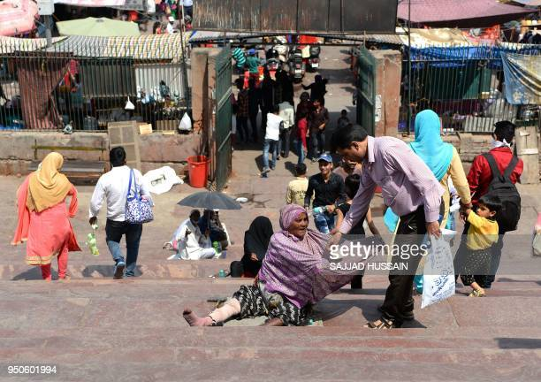 An Indian woman asks for alms on the stairs of the Jama Masjid mosque in the old quarters on New Delhi on April 24 2018