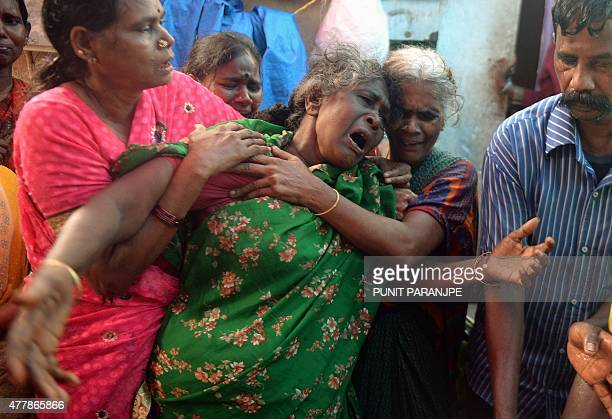 An Indian woman breaks down as she sees the dead body of her family member a victim of toxic homemade liquor consumption in Mumbai on June 20 2015...