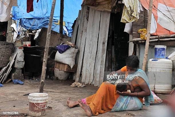An Indian woman breastfeeds her baby sits in front of her dilapidated hut in Hyderabad on July 11 2010 'Everyone counts' is the theme for this year's...
