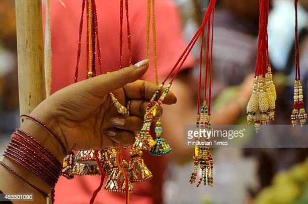 An Indian woman buys Rakhis ahead of Raksha Bandhan on August 7 2014 in Noida India The festival of Raksha Bandhan' or 'Rakhi' celebrate the...