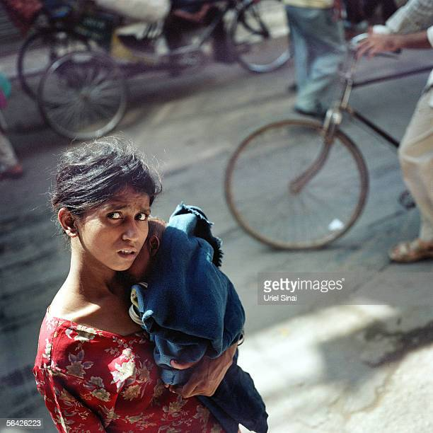 An Indian woman carries her infant child along a busy street September 26, 2005 in New Delhi, India. Although India occupies only 2.4% of the world's...