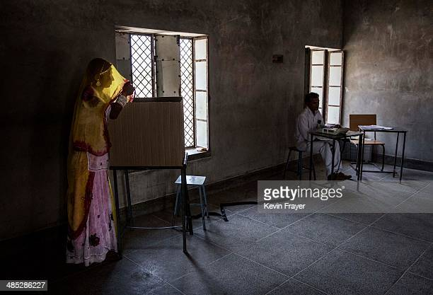 An Indian woman casts her ballot at a polling station on April 17 2014 in the Jodhpur District in the desert state of Rajasthan India India is in the...