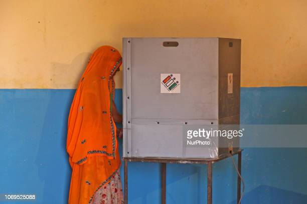 An Indian woman casts her vote at a local polling station for the state Assembly elections at Raisar Village of Jaipur District Rajasthan India on...