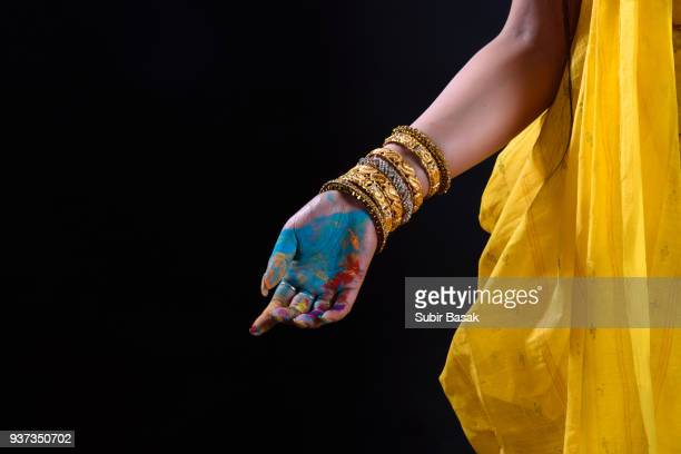an indian woman celebrating holi with colors - バングル ストックフォトと画像
