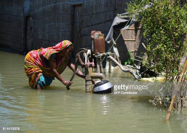 An Indian woman collects drinking water from a hand pump in the flood affected Kamrup district of Assam state on 14 July 2017 / AFP PHOTO /