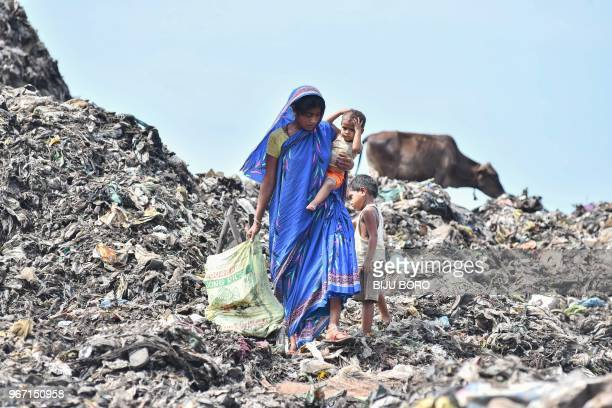 TOPSHOT An Indian woman collects fire woods as she carries her child at one of the largest disposal sites in northeast India ahead of the 'World...